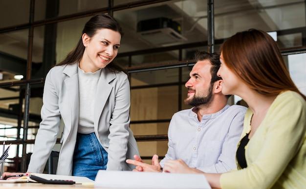 Sonriendo empresarios trabajando juntos en la oficina Foto gratis
