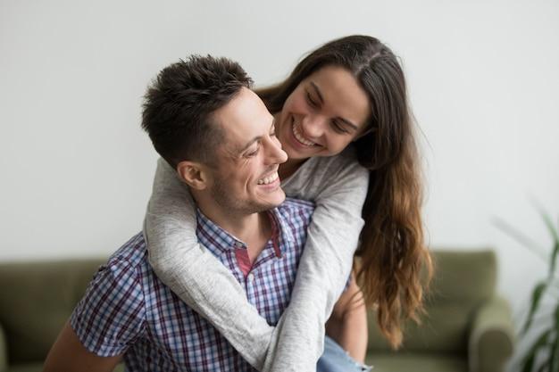 Sonriendo esposa riendo abrazando joven marido a cuestas en su casa Foto gratis