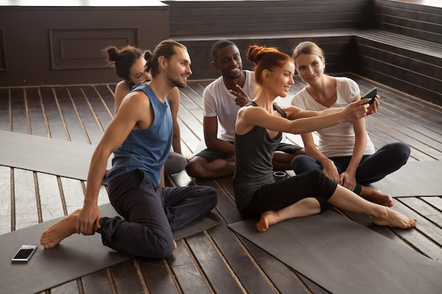 Sonriendo gente multirracial haciendo selfie en smartphone en yoga t Foto gratis