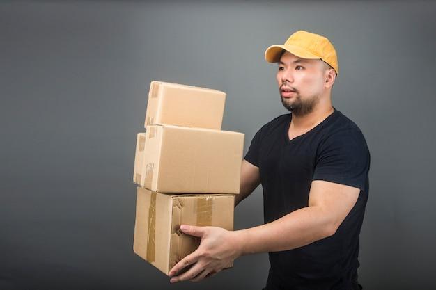 Sonriendo guapo asiático entrega hombre llevaba gorra, dar y llevar paquete, caja de cartón, día de la casa móvil y concepto de entrega urgente Foto Premium