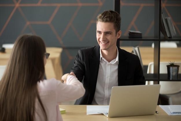 Sonriendo hr empleador apretón de manos empleo exitoso solicitante de contratación o saludo Foto gratis
