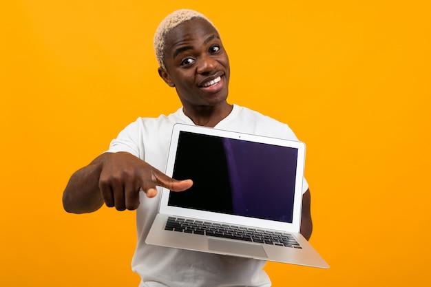 Sonriendo lindo estadounidense con cabello blanco en una camiseta blanca muestra una pantalla de computadora portátil con una maqueta y señala con el dedo hacia adelante en un estudio naranja Foto Premium