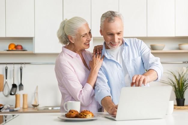 Sonriendo madura pareja amorosa familia usando la computadora portátil Foto gratis