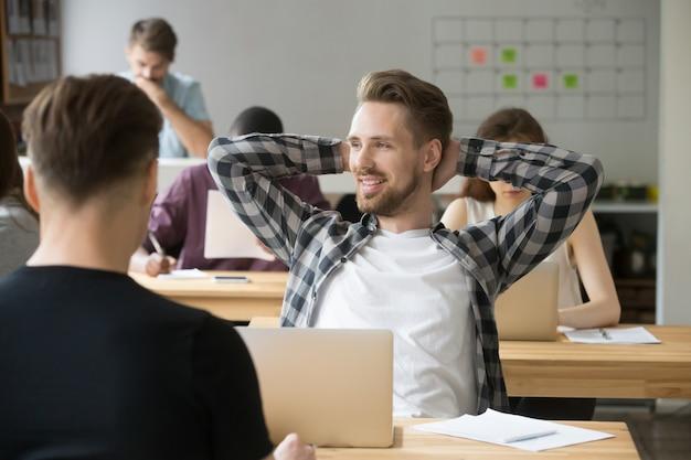 Sonriendo manos relajantes de hombre detrás de la cabeza disfrutando de trabajo en co-trabajo Foto gratis