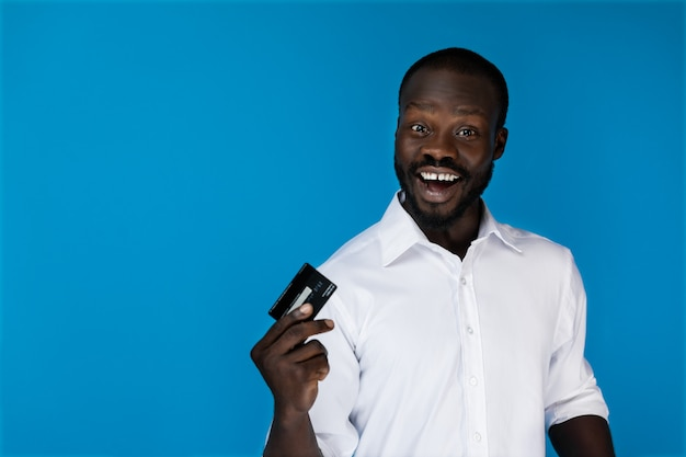 Sonriendo mirando hacia adelante hombre afroamericano en camisa blanca tiene tarjeta de crédito en una mano Foto gratis