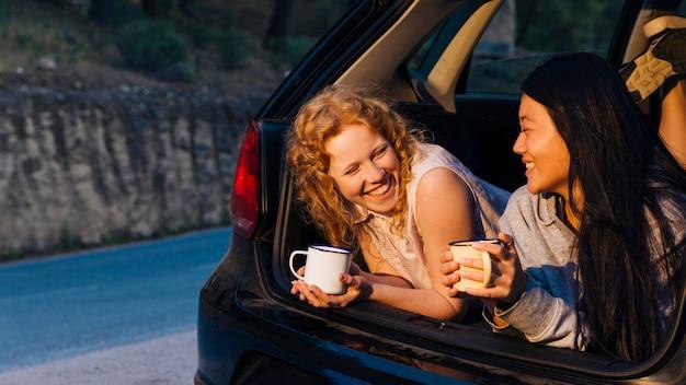 Sonriendo multiétnicas mujeres jóvenes hablando en maletero abierto Foto gratis