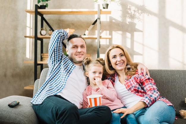 Sonriendo padres e hija viendo la televisión sentado en el sofá Foto gratis
