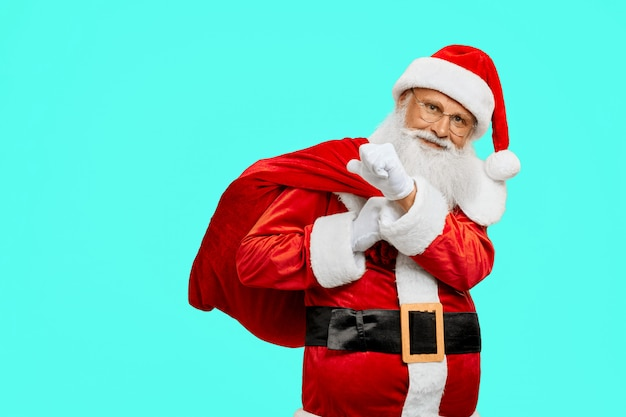 Sonriendo santa claus con bolsa con regalos. Foto gratis