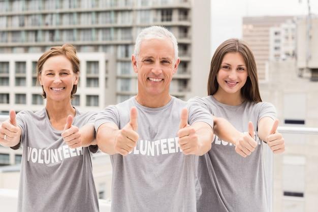 Sonriendo voluntarios haciendo pulgares arriba Foto Premium