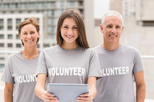 Sonriendo voluntarios con tableta Foto Premium