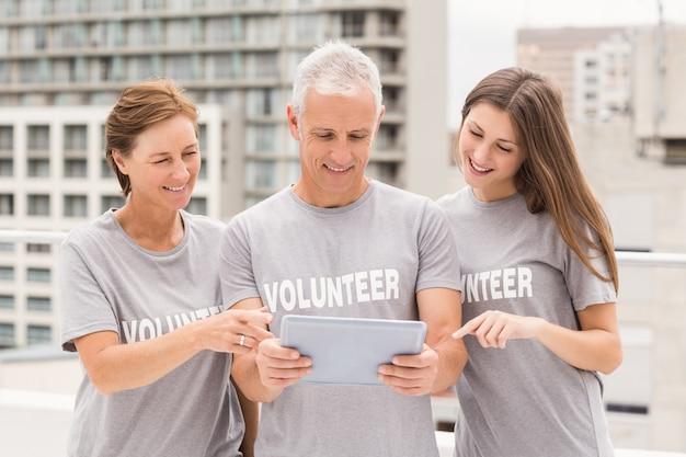 Sonriendo voluntarios usando tableta juntos Foto Premium