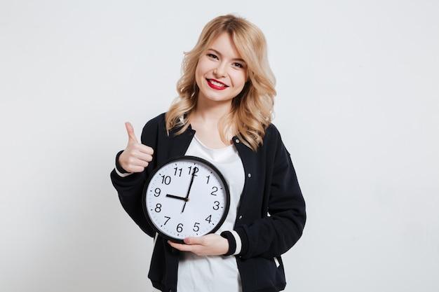 Sonriente casual joven adolescente sosteniendo el reloj y mostrando el pulgar hacia arriba Foto gratis