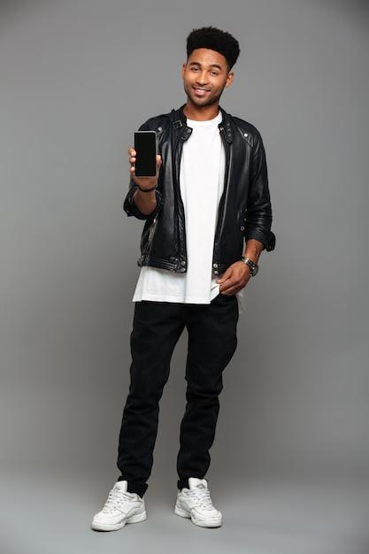 Sonriente chico africano de moda de pie con la mano en el bolsillo mientras muestra la pantalla del móvil en blanco, mirando Foto gratis