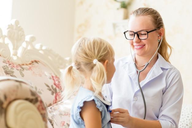 Sonriente doctora escuchando a niña Foto gratis