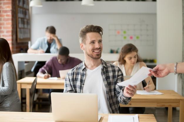 Sonriente empresario guapo dando documento financiero a compañero de trabajo. Foto gratis