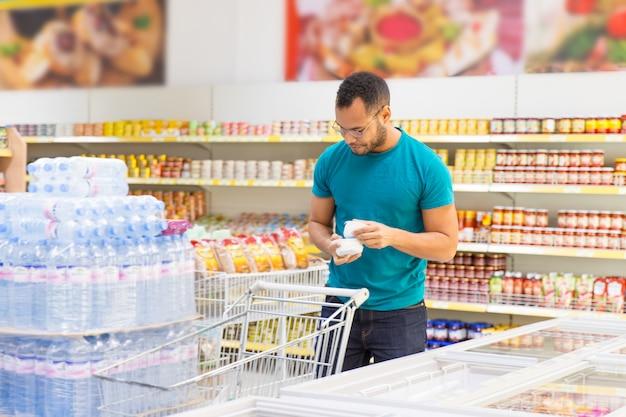 Sonriente hombre afroamericano tomando productos del congelador Foto gratis
