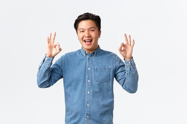 Sonriente hombre asiático satisfecho con tirantes en camisa azul, mostrando un gesto bien, felicitando a la persona con un trabajo excelente, bien hecho, recomiendo un servicio perfecto o calidad, pared blanca Foto gratis