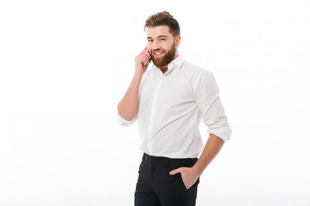 Sonriente hombre barbudo en ropa de negocios hablando por teléfono inteligente Foto gratis