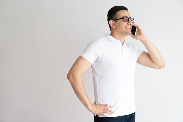 Sonriente hombre guapo hablando por teléfono inteligente. joven llamando por teléfono celular. Foto gratis