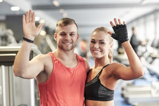 Sonriente hombre y mujer agitando las manos en el gimnasio Foto Premium