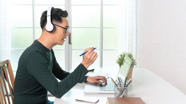 Sonriente hombre de negocios asiático guapo usa auriculares trabajando de forma remota desde casa. él es una videoconferencia de seminarios web Foto gratis