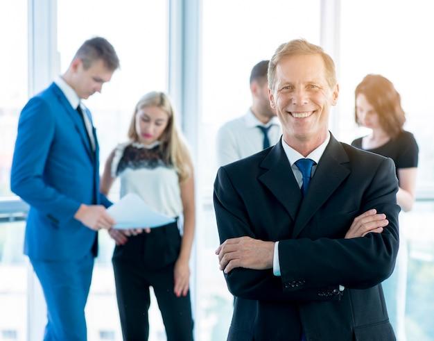 Sonriente hombre de negocios maduro de pie delante de sus colegas en el lugar de trabajo Foto gratis