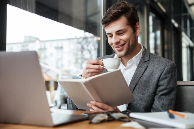 Sonriente hombre de negocios sentado en la mesa de café con computadora portátil mientras lee el libro y bebe café Foto gratis