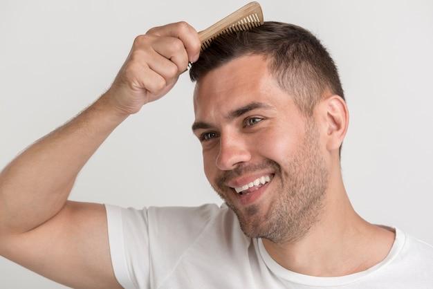 Sonriente hombre rastrojo peinarse contra el telón de fondo blanco Foto gratis