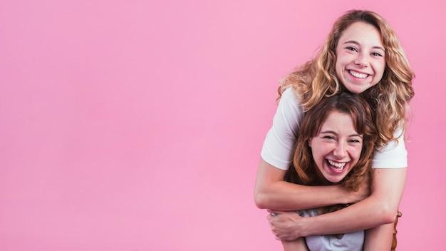 Sonriente joven abrazando a su amiga por detrás contra el fondo rosa Foto gratis