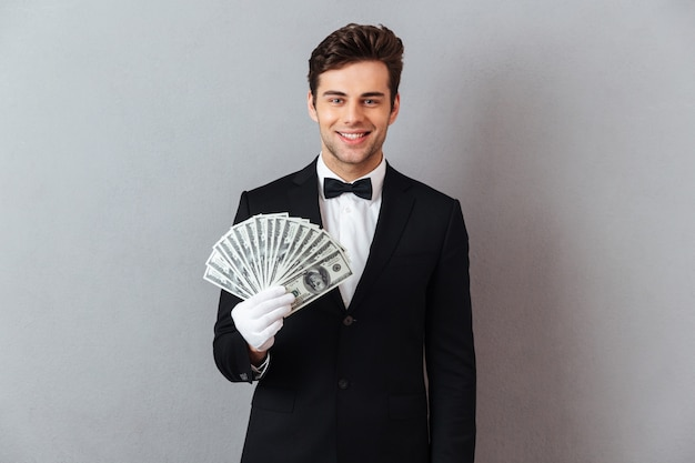 Sonriente joven camarero con dinero. Foto gratis