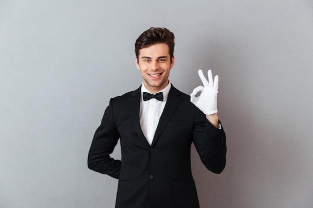 Sonriente joven camarero mostrando gesto bien. Foto gratis