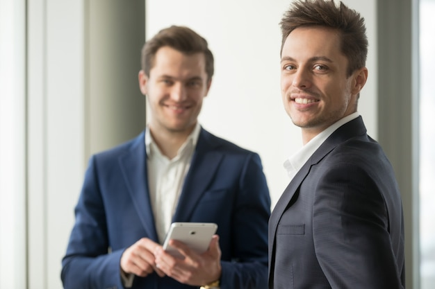 Sonriente joven empresario mirando a cámara, desarrollar aplicación Foto gratis