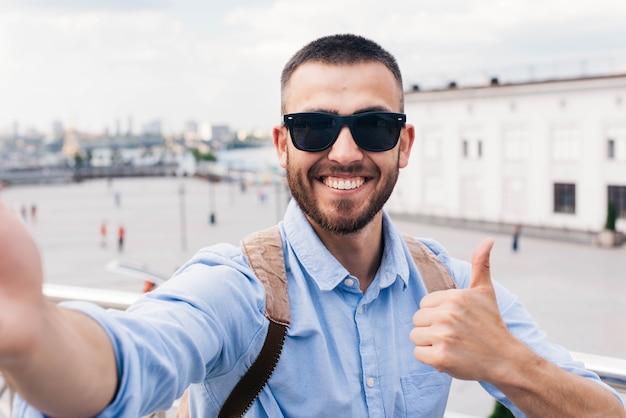 Sonriente joven con gafas de sol tomando selfie y mostrando el pulgar hacia arriba gesto Foto gratis
