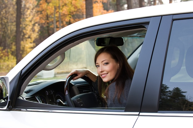 Sonriente joven hermosa mujer sentada en el coche nuevo Foto gratis