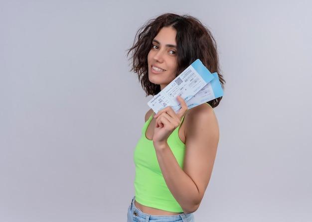 Sonriente joven hermosa mujer viajero sosteniendo billetes de avión de pie en la vista de perfil en la pared blanca aislada con espacio de copia Foto gratis