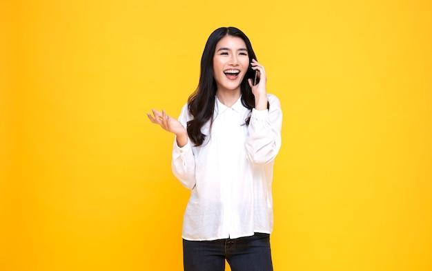 Sonriente joven mujer asiática casual hablando teléfono inteligente aislado sobre fondo amarillo. Foto Premium