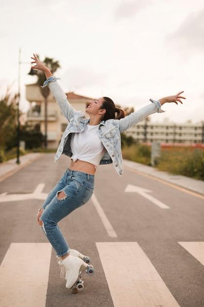 Sonriente joven mujer patinadora bailando con patín en el camino Foto gratis