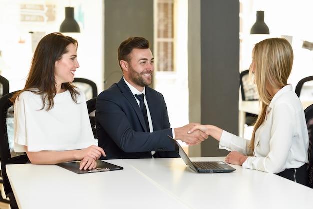 Sonriente joven pareja agitando las manos con un agente de seguros Foto gratis