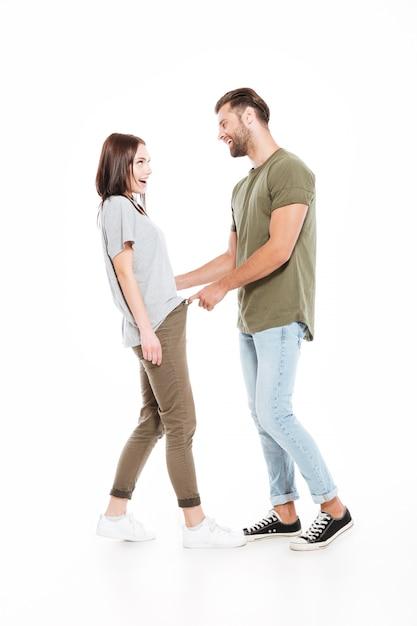 Sonriente joven pareja amorosa de pie aislado Foto gratis