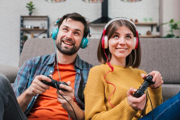 Sonriente joven pareja con auriculares en la cabeza jugando al videojuego Foto gratis