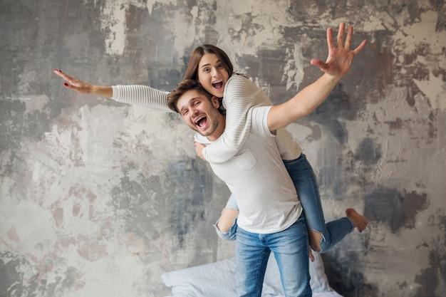 Sonriente joven pareja jugando en la cama en casa en ropa casual, hombre y mujer divirtiéndose juntos, emoción positiva loca, feliz, levantando la mano Foto gratis