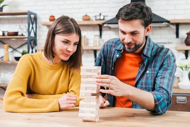 Sonriente joven pareja jugando la torre de bloques de madera juego en casa Foto gratis
