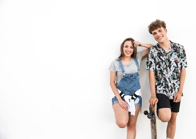Sonriente joven pareja con patín sobre fondo blanco Foto gratis
