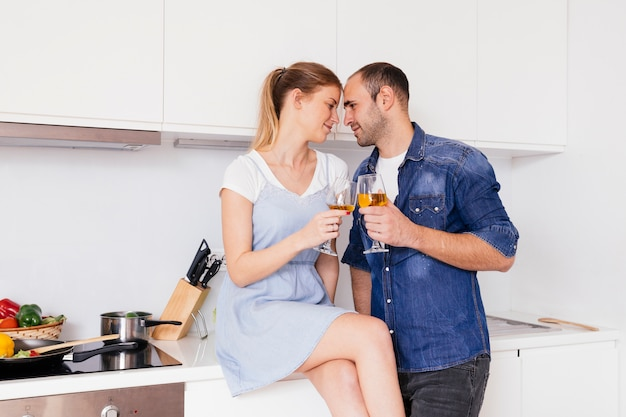 Sonriente joven pareja romántica brindando las copas en la cocina Foto gratis
