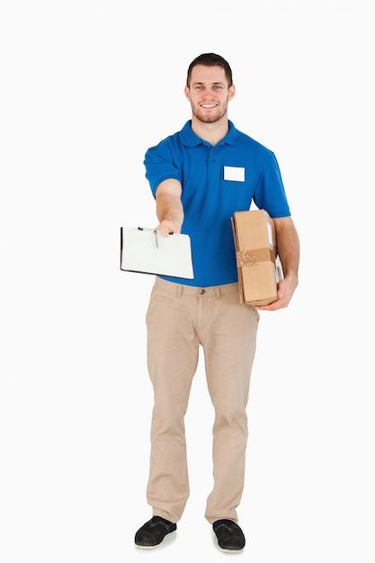 Sonriente joven vendedor con paquete pidiendo firma Foto Premium