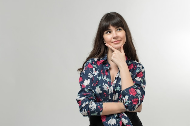 Sonriente jovencita en camiseta diseñada de buen humor con el pelo largo en blanco Foto gratis