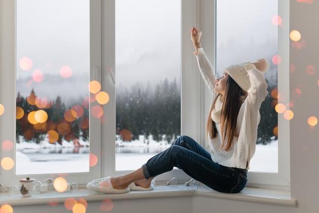 Sonriente mujer atractiva joven feliz en elegante suéter de punto blanco, bufanda y sombrero sentado en casa en el alféizar de la ventana en navidad divirtiéndose sosteniendo las manos, vista de fondo del bosque de invierno, luces bokeh Foto gratis