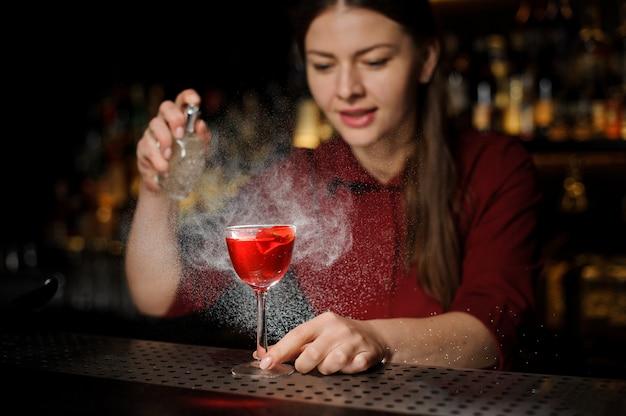 Sonriente mujer barman rociando un vaso de cóctel lleno de sabrosa jeringa aperol cóctel de verano con un whisky pelado Foto Premium