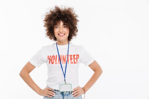 Sonriente mujer casual vestida con camiseta de voluntario con insignia Foto gratis