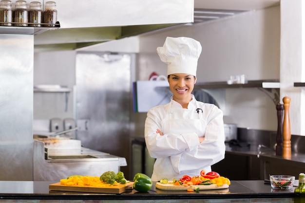Sonriente Mujer Chef Con Verduras Cortadas En La Cocina